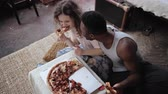 cardboard : Woman offers pizza to man, but eat slice by herself. Multiracial couple having fun during the meal with fast food.