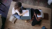 бросание : Top view of multiracial couple sitting on floor and playing board game. Woman throws dice, takes card. Man waits turn.
