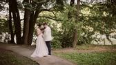 женат : Couple in love share their wedding day. They happily stand in a park and smell beautiful brides bouquet.