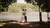 margem do rio : Lovers on a wedding day stand on a river bank looking at each other, kissing. Happy bride in a beautiful dress.