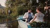 novomanželka : Lovers have a good time on their wedding day. Couple in love on a blue boat mooring to a river bank. Groom oars. Dostupné videozáznamy