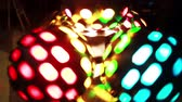 Боке : Close-up view of colored light disco ball twisting. Colored show at the disco club party. Rays of the scene light.