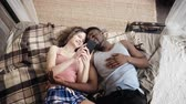 kultura mládeže : Multiracial couple lying on bed. Man and woman spend time together with joy and fan, use Smartphone, surf the internet.