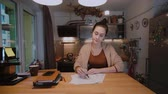 concentrando : Young businesswoman with documents sitting at the table and working with papers. Overtime work at home.