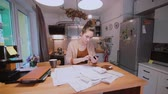dinheiro : Young woman sitting at the table in kitchen and calculating bills. Home accounts department. Checking the bills. Stock Footage