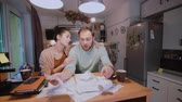 anger : Worried couple looking at their bills in the kitchen at home. Man and woman calculating domestic accounts. Stock Footage