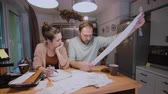 man spend money : Worried young family looking at their bills in the kitchen at home. Man and woman calculating domestic accounts. Stock Footage