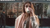 kétség : Young brunette woman with cup of coffee standing in front of show-window. Girl dreaming to buys clothes. Slow motion. Stock mozgókép