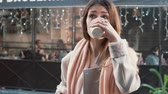 pochybovat : Attractive girl with cup of coffee standing in front of show-window. dreams to buy something, sighs. Slow motion.