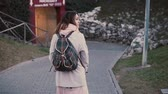chegar : Back view of woman with suitcase and backpack walking in the city at evening. Girl moving to new place. Slow motion.