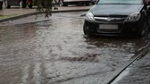 chovendo : Flooding water on a pavement after heavy rain with sound. Car is near, people walk by. Stock Footage