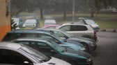flow : Heavy rain on cars and a lightning with sound. A man walking by with an umbrella. Stock Footage