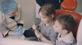 estomatologia : Two kids, boy and girl sitting in dentist chair before the dental check-up. Brother and sister mould with young doctor.