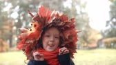 coroa : 4k close-up portrait of smiling cute little girl in a wreath crown of autumn maple leaves posing, making funny faces