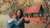 amarelo : young mother holding his cute little son, the boy puts food in the bird feeder in an amazing autumn park 4k