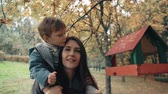 semente : young mother holds on the shoulders a cute little boy, the boy puts food in the bird feeder in an amazing autumn park 4k