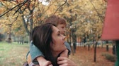 arbusto : young mother holds on shoulders cute little boy, little boy hugs her near bird feeders in amazing autumn park 4k