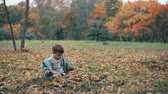 atender : cute little boy playing in the autumn park, sits on grass throws up yellow fallen leaves 4k