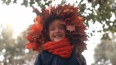 coroa : 4k close-up portrait of happy smiling beautiful cute little girl in a wreath crown of autumn maple leaves Stock Footage