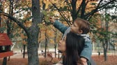 ombros : beautiful young mother holds on the shoulders a cute little son, boy plucks red berries from a tree in autumn park 4k