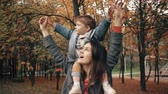 семена : beautiful young mother holds on the shoulders a cute little son, the boy point the finger at something in autumn park 4k
