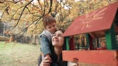 feeder : young mother holds on shoulders cute little boy, little boy hugs kisses her near bird feeders in amazing autumn park 4k Stock Footage