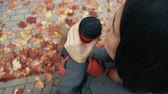 contraste : Autumn beautiful maple leaves. Top view of young stylish woman sitting in city park drinking coffee 4k