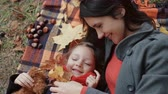 miś : beautiful mother with her cute little daughter lying on the plaid playing with maple leaves in autumn park 4k Wideo