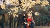 листва : cute, laughing, funny cheerful little girl with teddy bear shakes branch of a tree and yellow autumn leaves fall from it