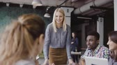 participation : Young blonde woman manager talking with mixed race team. Businesswoman giving direction to colleagues at modern office. Stock Footage