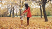 movimentar se : young beautiful mother turns her cute little son around holding his hand in autumn park slow mo Vídeos