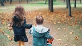 brasão : back view cute brother and sister little boy and girl running holding hands with their toys through autumn alley slow mo
