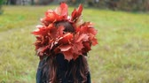 contraste : back view cute little girl in a wreath crown of autumn maple leaves walks in the park slow motion