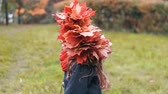 grimasa : Girl goes back and then turns around and looks at the camera. cute little girl in a wreath crown of autumn maple leaves.