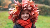 coroa : close-up portrait of happy smiling beautiful cute little girl in a wreath crown of autumn maple leaves slow motion