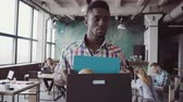 безработные : Young african man get fired from work at start-up. Male walks through the office, carrying box with personal belongings.