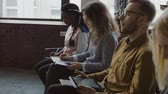 attention : Multiethnic team sitting at loft office and listening the business seminar. Young man and woman with tablet makes notes. Stock Footage