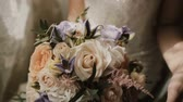 flora : Young beautiful bride holding the wedding bouquet. Close-up view of female touching the flowers before ceremony. Stock Footage