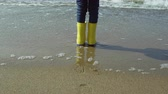 özlem : Close-up view of little girl foot in bright yellow rubber boots. Child standing on shore of beach, footprints in sand. Stok Video
