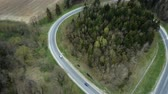 экологический : Aerial drone view of the traffic countryside roadway near the green forest. Cars drive through the fork.
