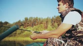 inflável : Young man sits in the boat at forest lake and throws a rod. Attractive male catching fish with rod with spinning reel. Vídeos