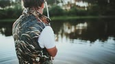 isca : Young man catching fish in the rubber boat at the lake. Male throws a fishing rod into the water and twists the reel. Stock Footage