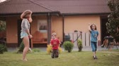 jumping : Little brother and sister repeating after elder sister. Family dancing on the backyard outside on the summer day. Stock Footage