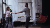 jumping : Multiracial couple in pajamas dancing, having fun together in morning. Woman jumps on man hands, kisses. Slow motion.