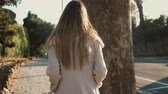 életmód : Back view of young woman walking alone at the city centre. Pensive female going near the road in bright sunny day.