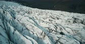 mudança : Copter fly over the ice ridge in Iceland. Close-up aerial view of white glacier Vatnajokull with black ash.