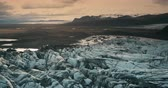 extremo : Aerial view of the ice lagoon on sunset. Copter flying over the glacier Vatnajokull with volcanic ash in Iceland.