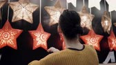 consumismo : Young attractive brunette girl at the store chooses lamps Star Lights, Christmas decor. Stock Footage