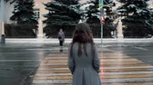 tristeza : Back view. The sad young brunette girl is waiting the green light to cross the road in a winter snow-covered city.
