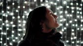 front : young attractive woman enjoying falling snow at Christmas night in front of the decorative wall full of sparkling lights